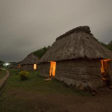 Night time shot of a traditional Fijian bure or homes made with thatched roofs and natural material walls.