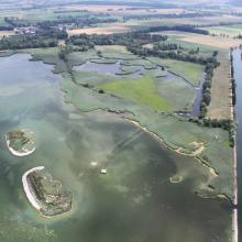 La baie sur la rive orientale du lac de Neuchâtel avec les deux îles, la lagune, et les zones humides du Fanel, le canal de la Broye et une partie du Chablais de Cudrefin (à droit du canal) .
