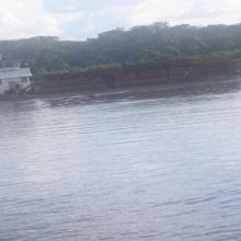 Un bateau transporteur de produits forestiers navig uant sur la rivière Sangha
